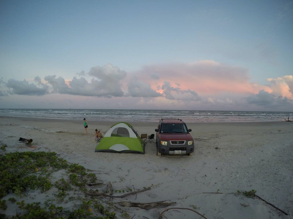 Tent set up beside car on the beach at sunset.