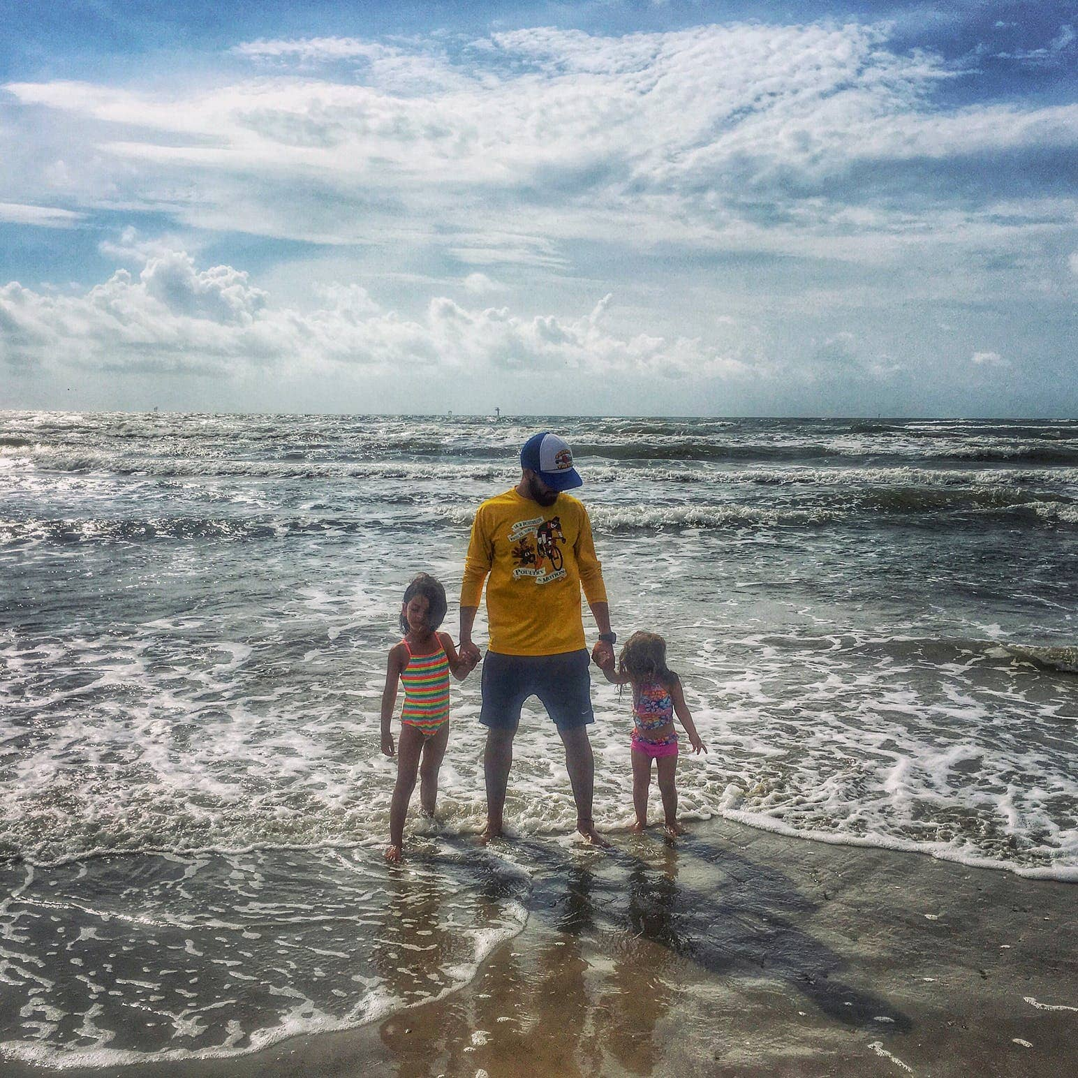 Two young girls holding their dads hands while wading through the beach on a sunny day.