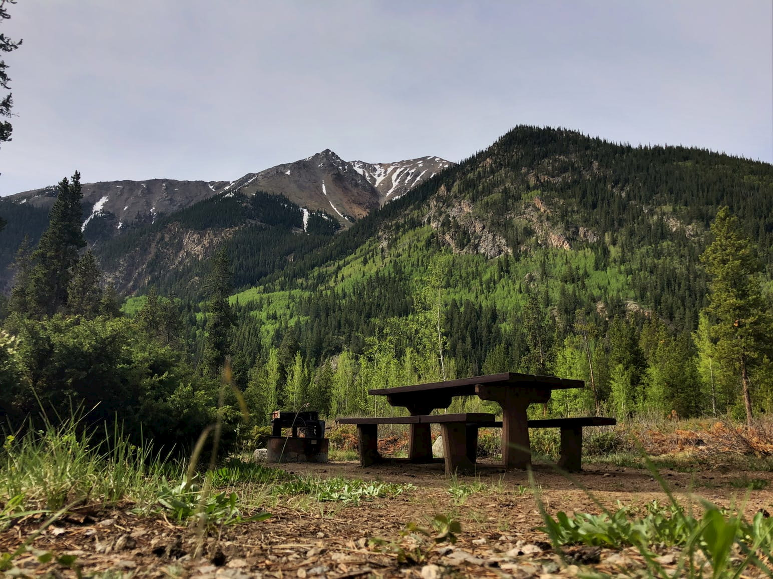 Picnic table and fire ring sit below epic mountain range with snow patches.