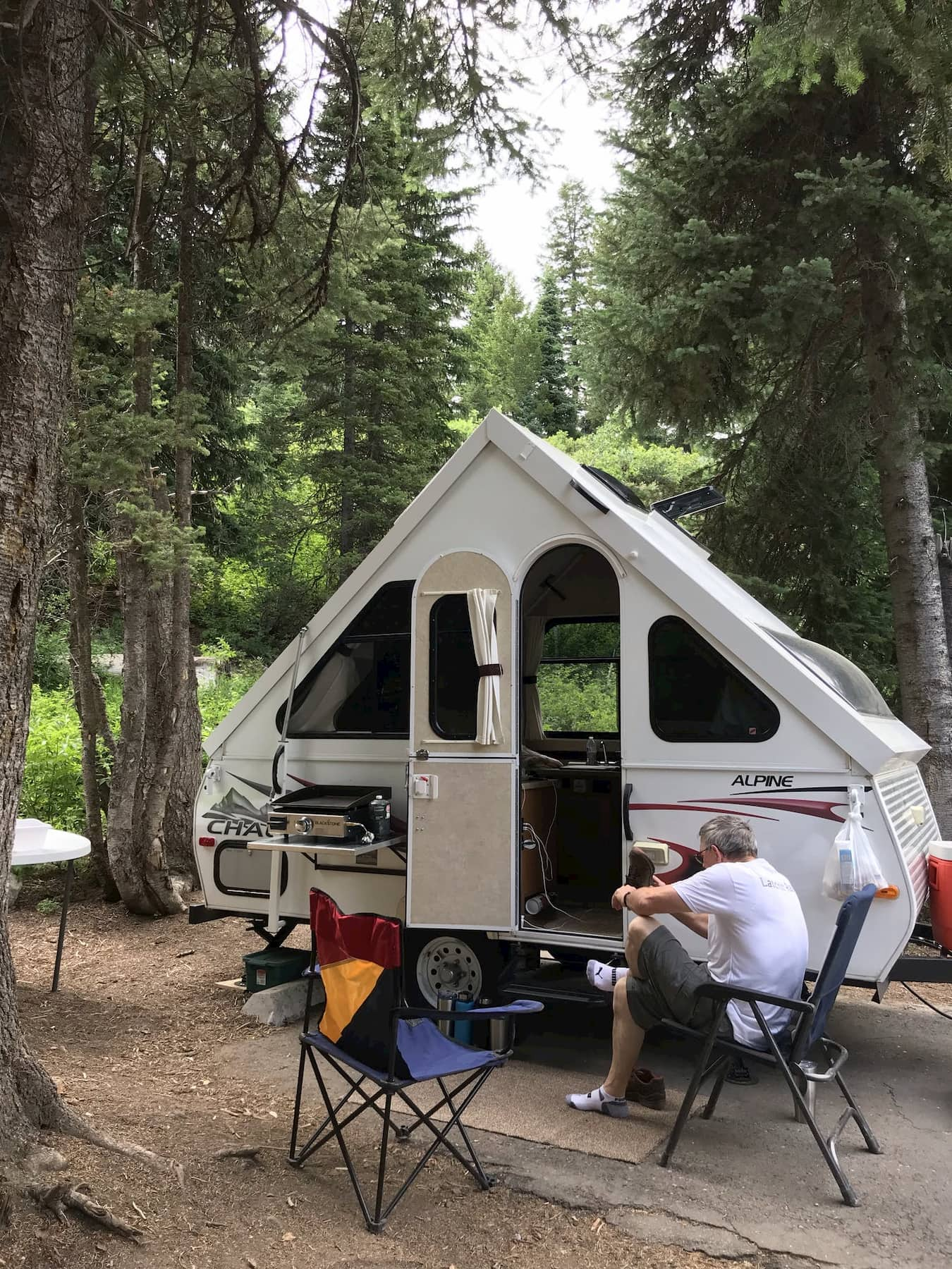 Man sitting in camping chair in front of A-line trailer in the forest.