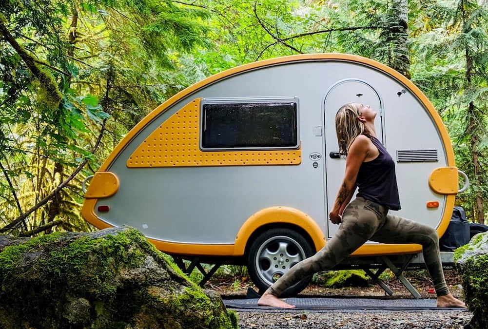 Woman doing yoga in front of yellow and gray trailer