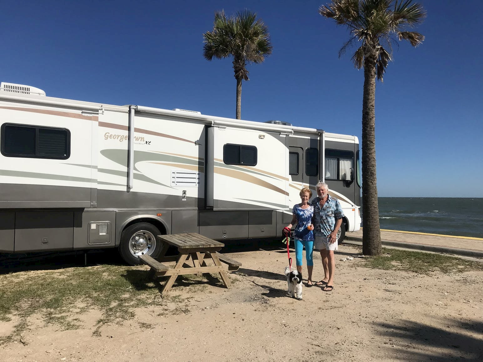 Couple and their dog pose in front of RV parked along a tropical beach.
