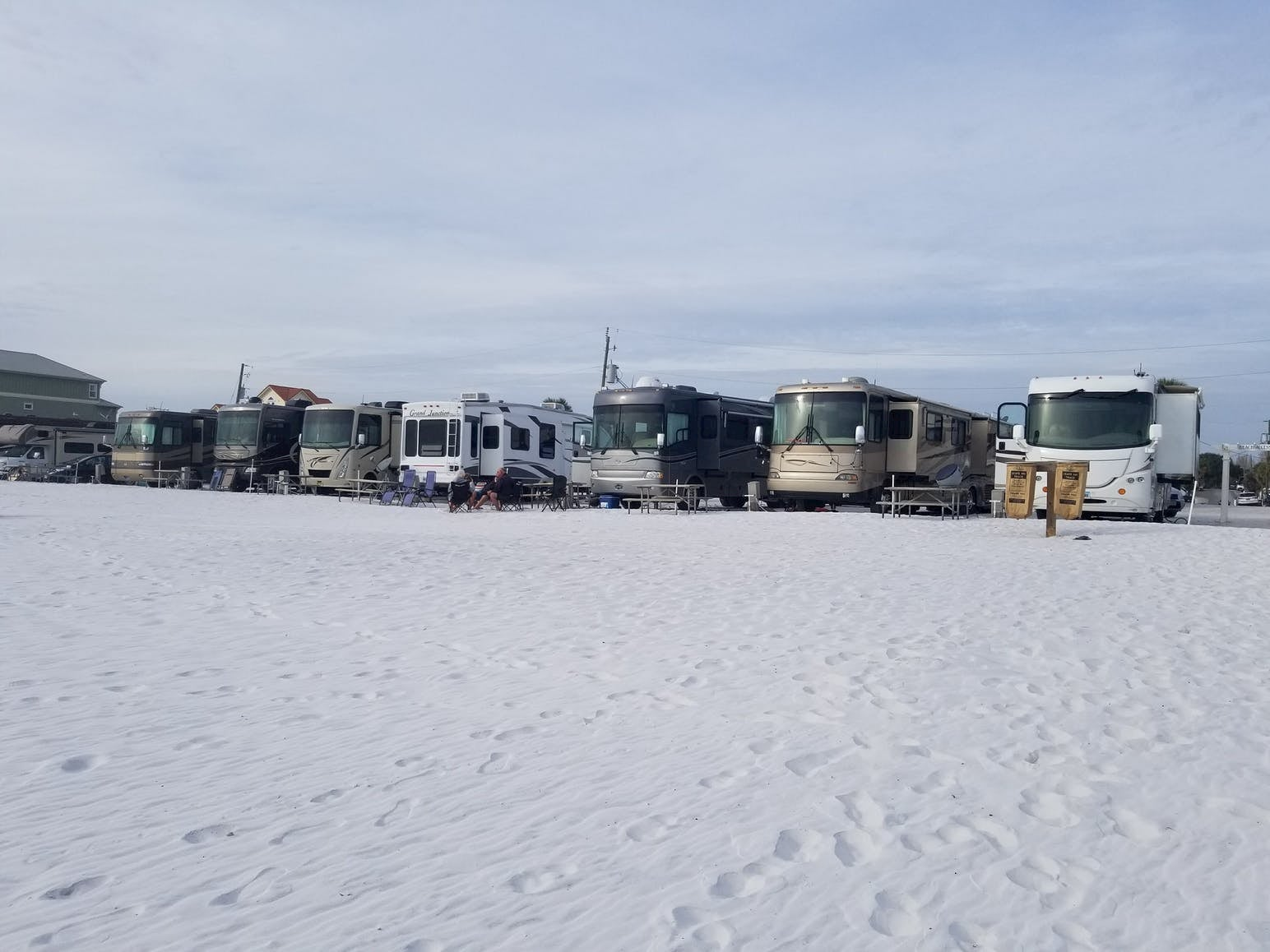 RVs lined up on white sand beach.