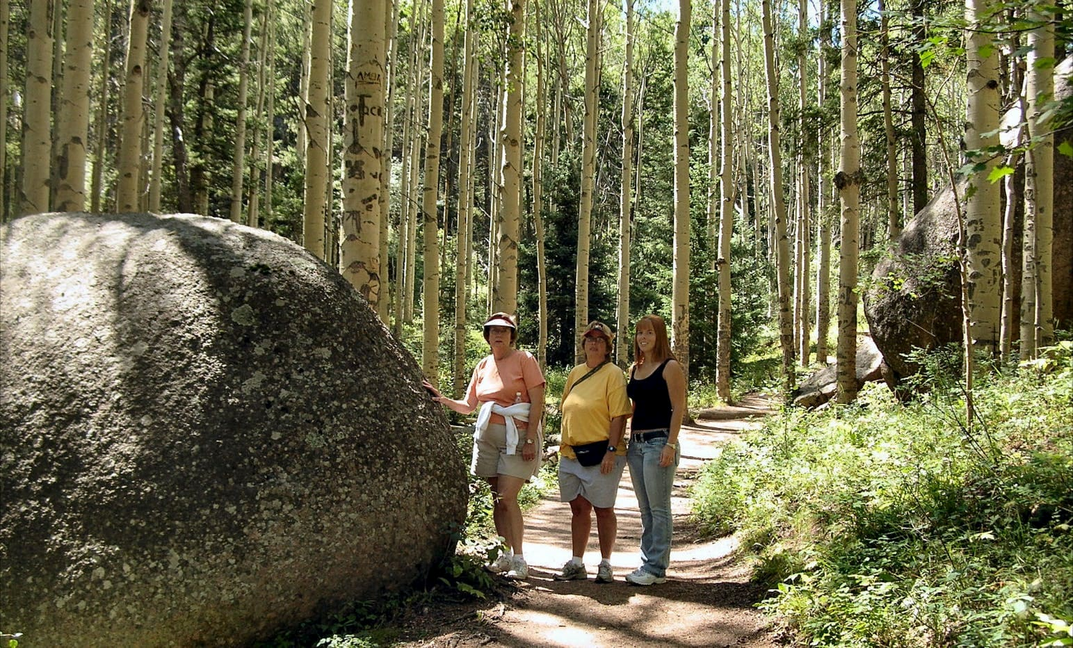 Group of three women hikers standing beside a boulder in the forest.