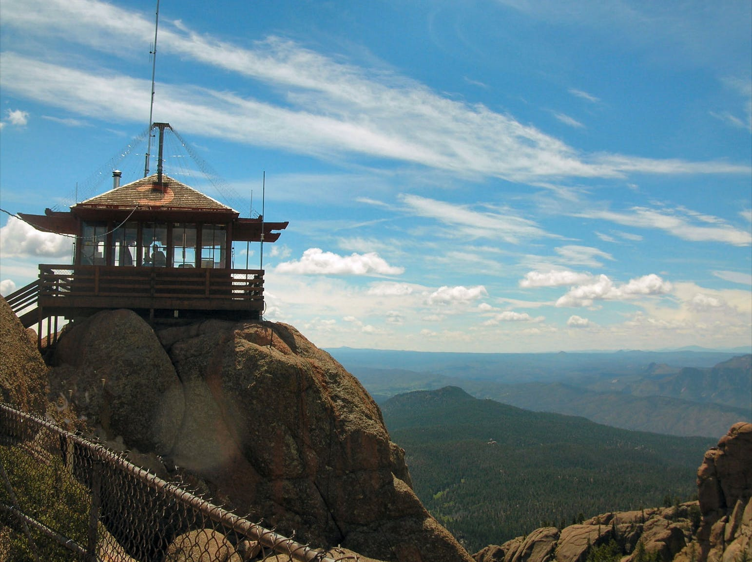 Fire tower sitting on rock cliff over mountain landscape.