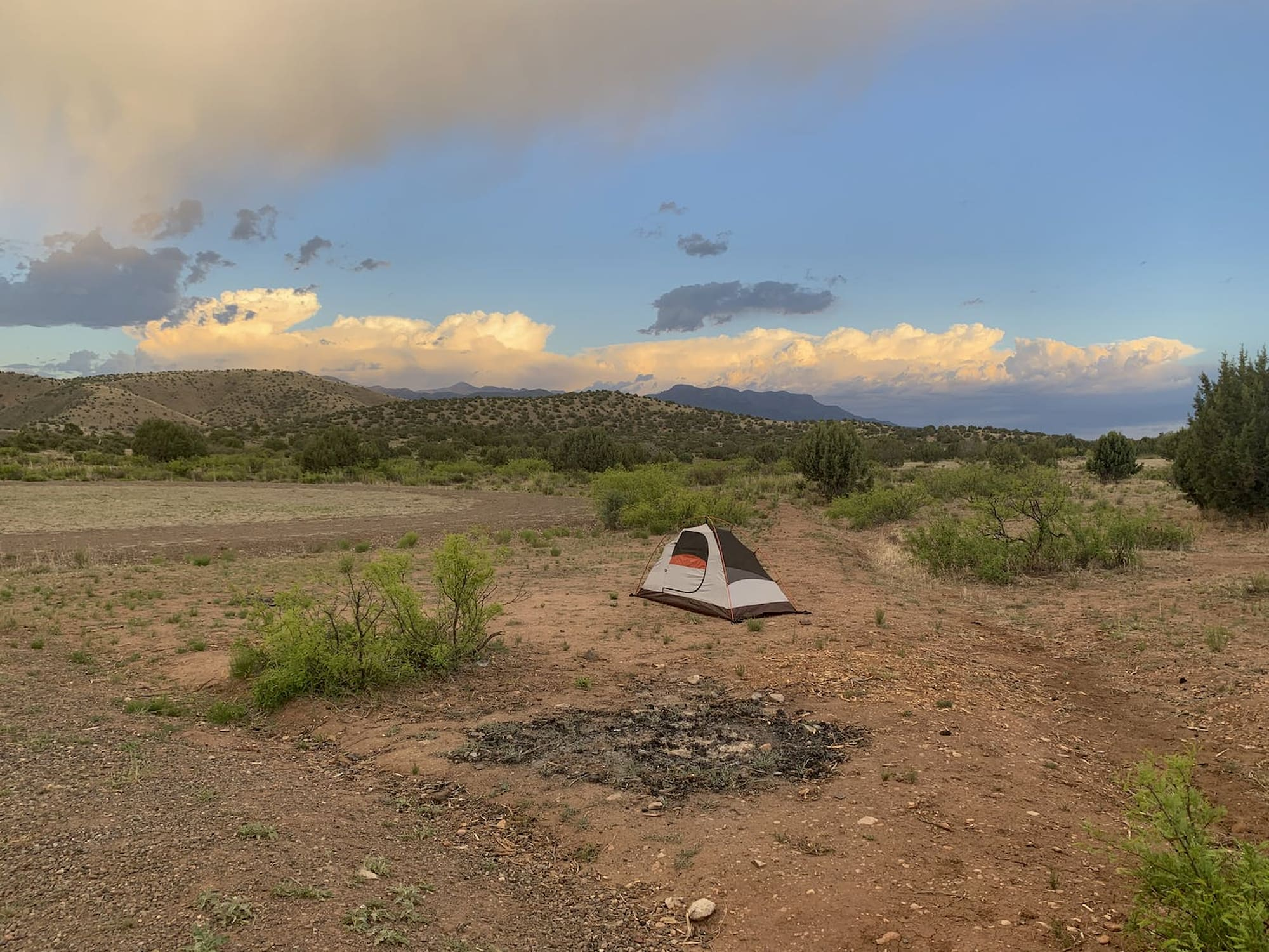 Small tent setup in expansive mountain desert landscape.