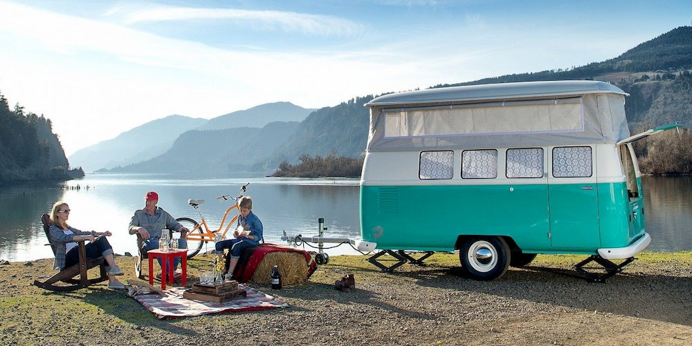 Family next to lake with turquoise vintage camper