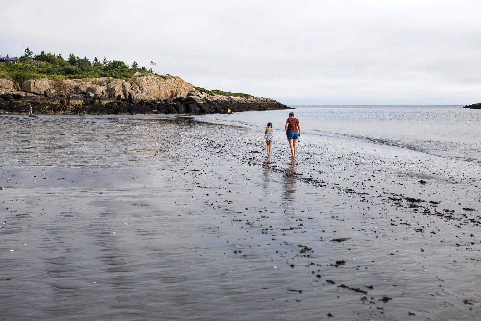 Two people walking on the beach on the coast of Hermit island, Maine.