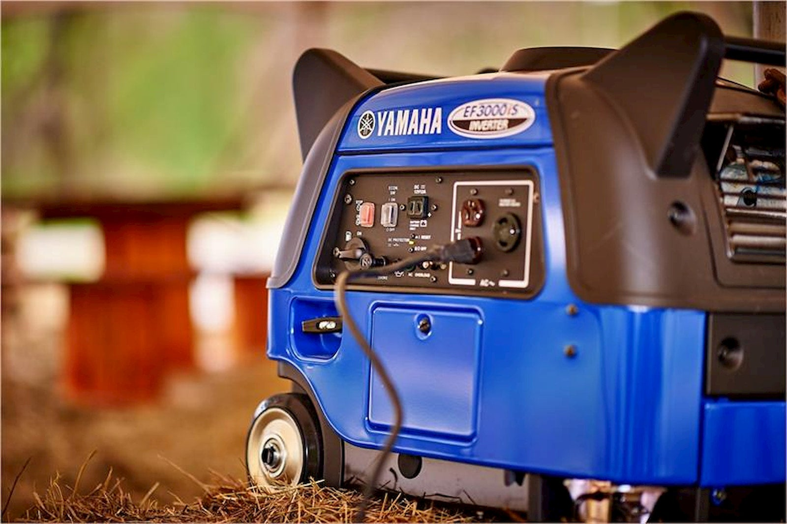 Blue generator on wheels on grass.