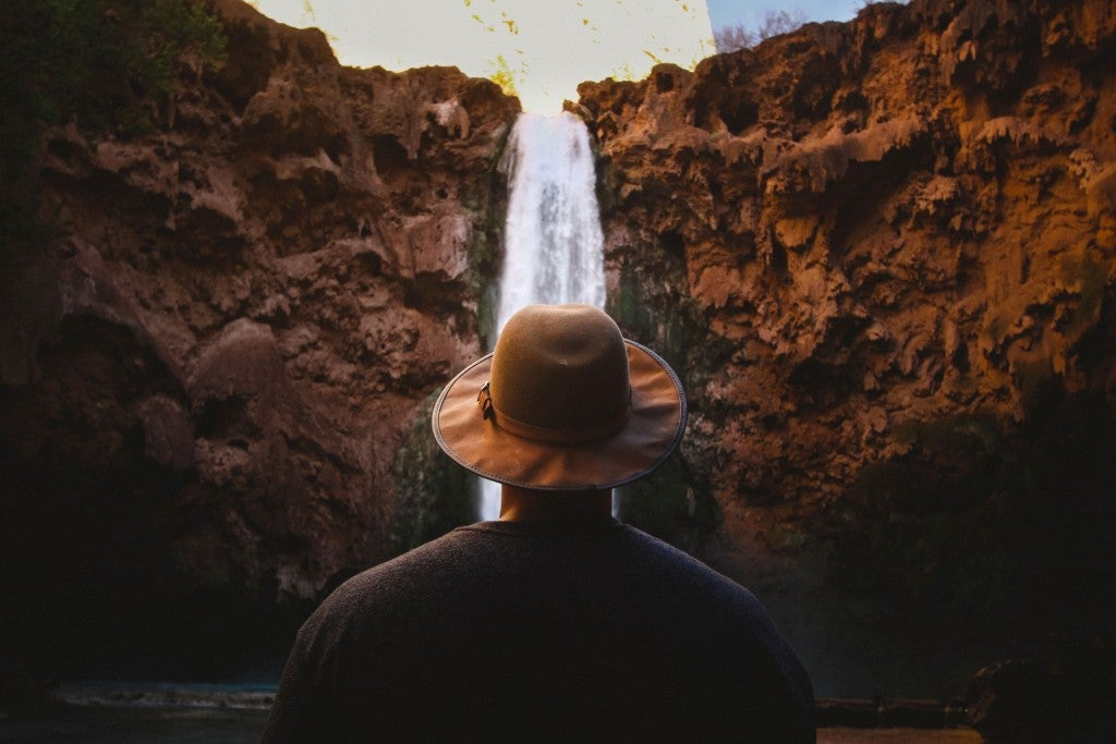Man with hat standing in front of cascading waterfall.