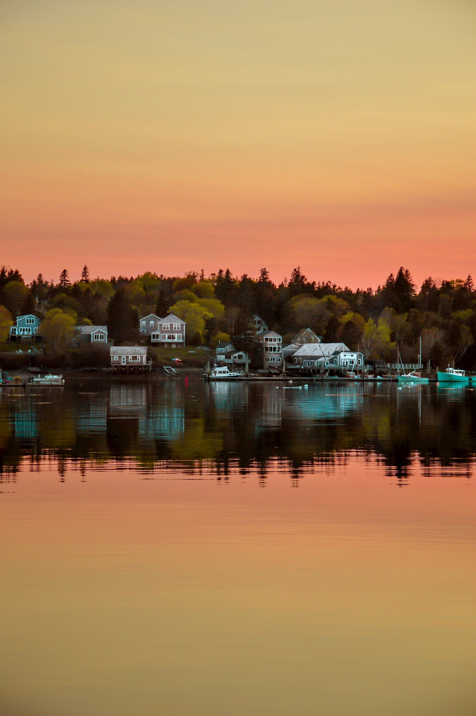 Sunset reflects upon water on island in Maine with cluster of waterfront houses.