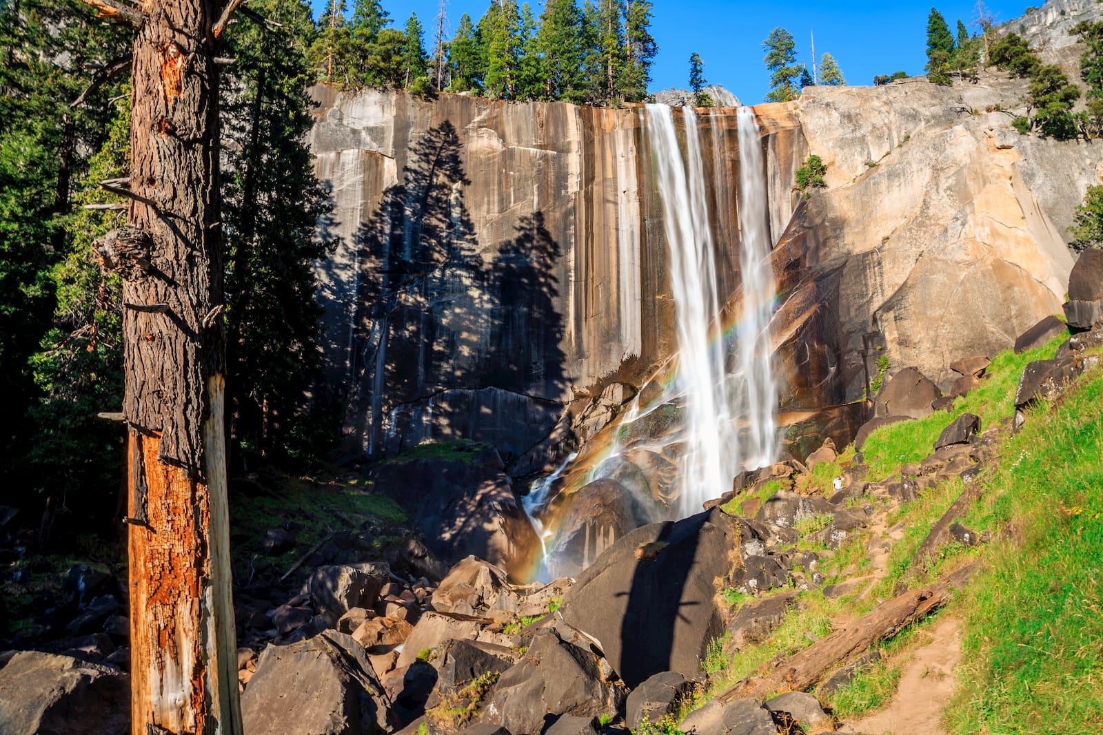 rainbow shimmering withing a waterfall crashing onto rocks below.