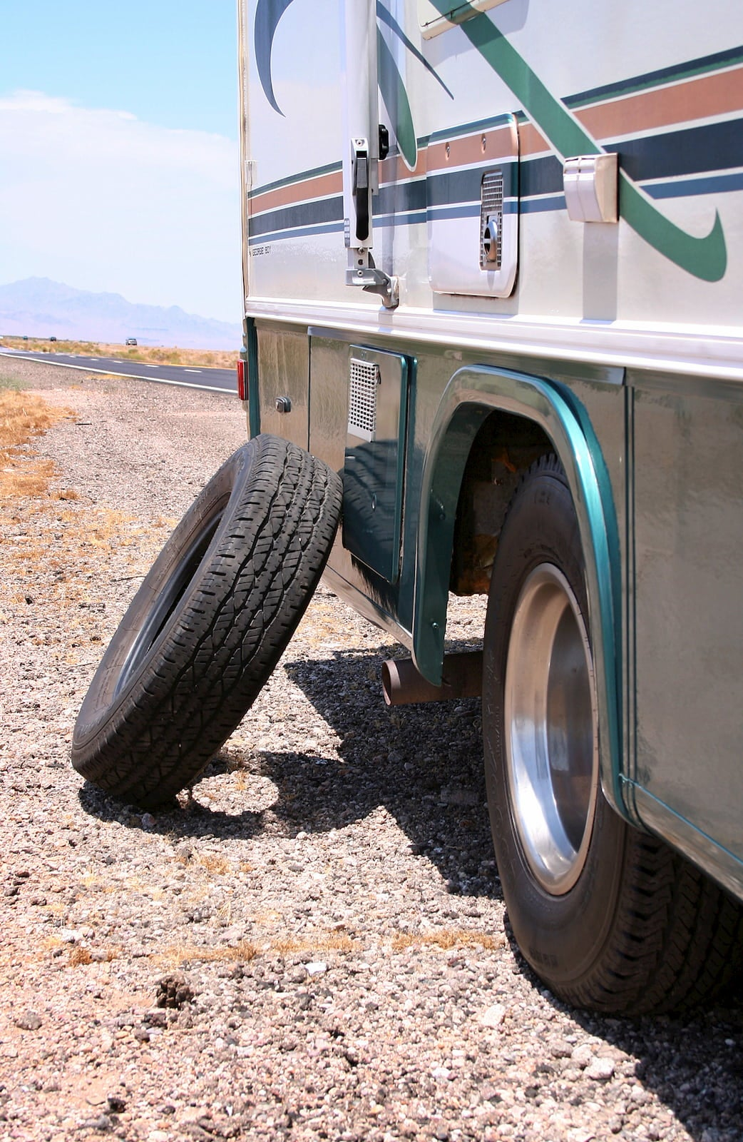 RV parked on the side of the road with tire leaning against it.