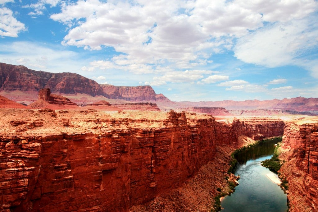 Landscape of river ruing through red rod cliffs in an expansive cayon.