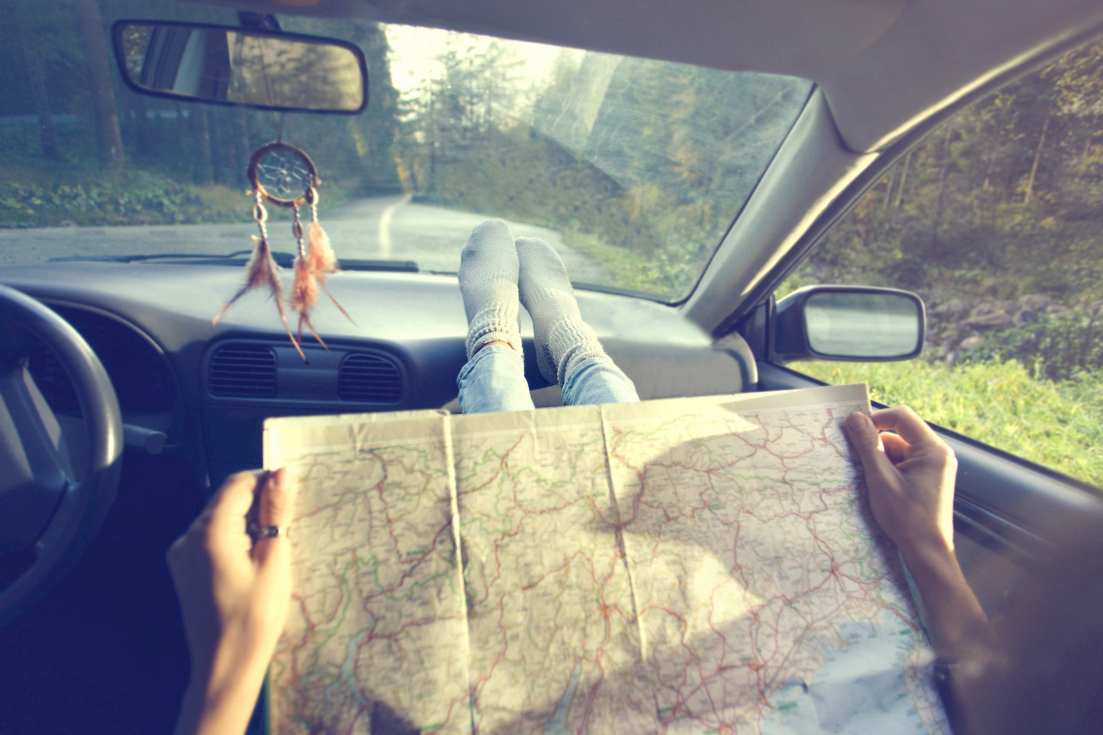 Person navigating using paper map while driving.