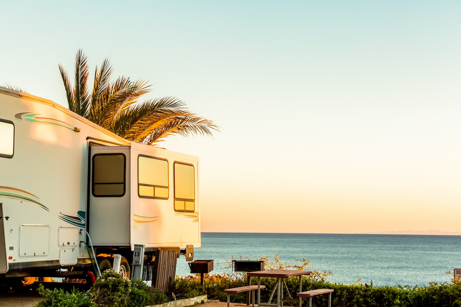 RV with slide out side parked on the beach.