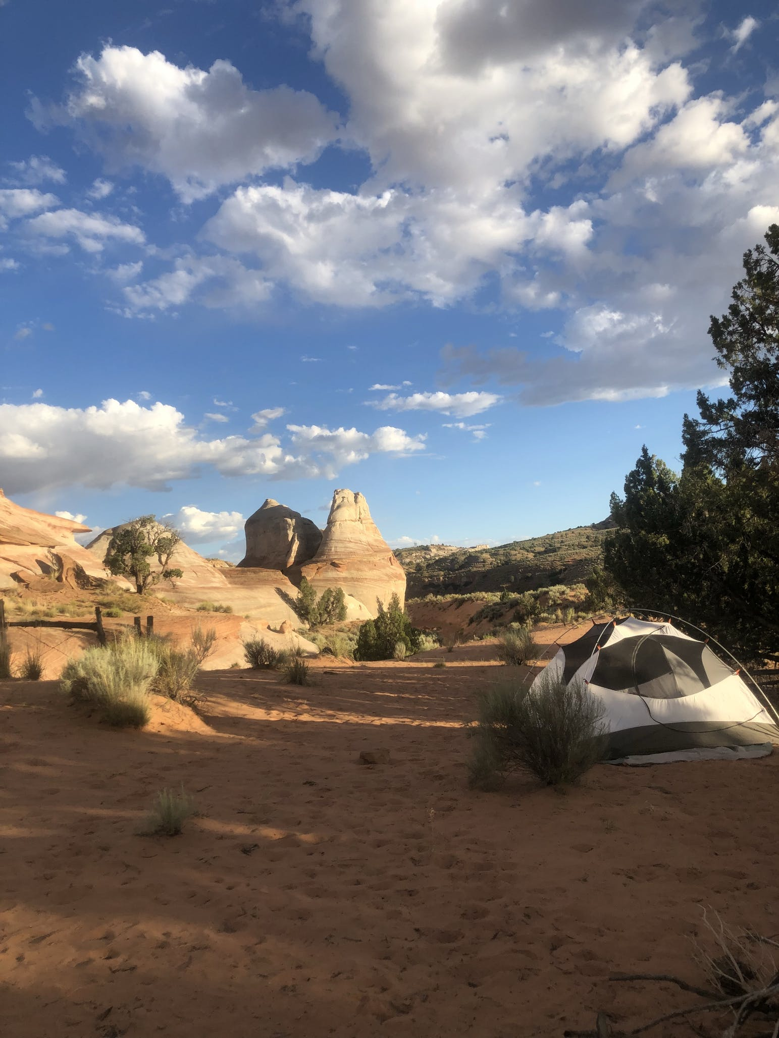 Tent beside rock formations at a desert campsite.