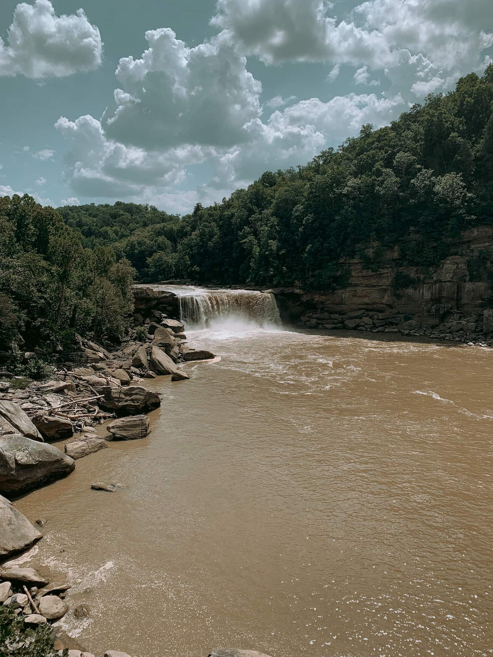 Waterfall pouring over muddy water under a cloudy bright blue sky.