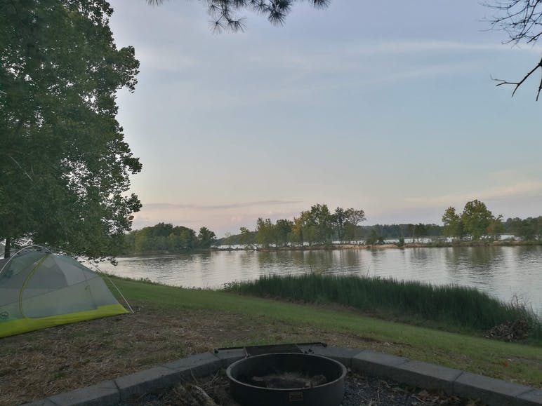 distant sunset on the river with tent in foregorund