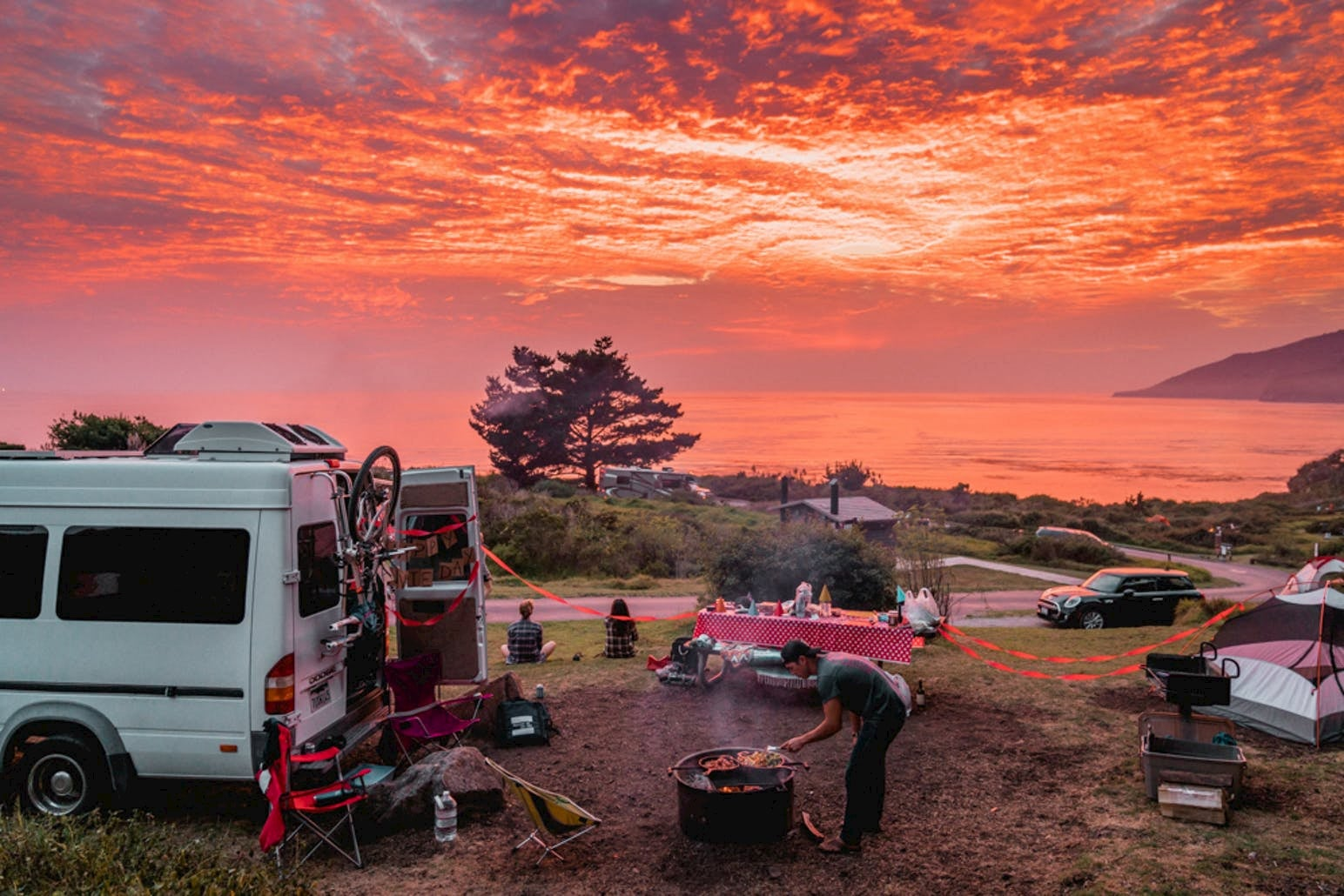 Bright pink sky during sunset with a group of van lifers sitting below near the coast around a fire and picnic table in Big Sur.