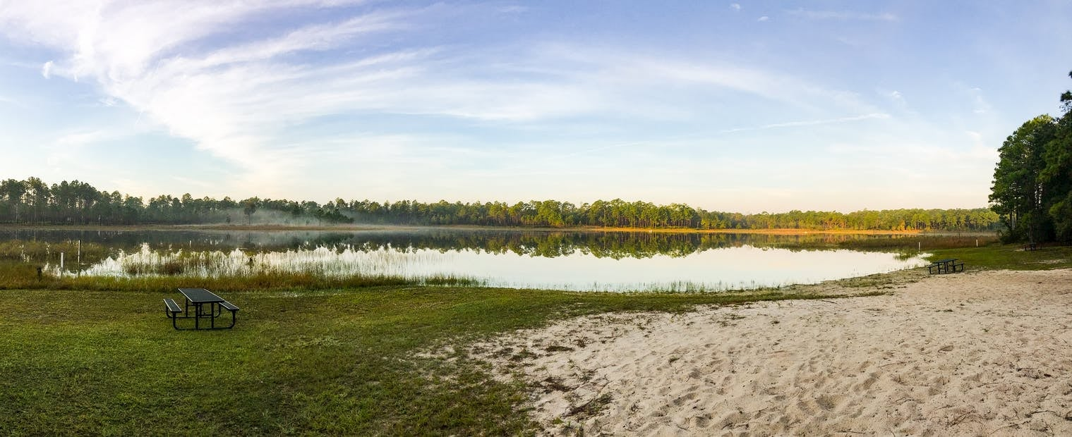 Panoramic image of lakeside campsite with picnic table.