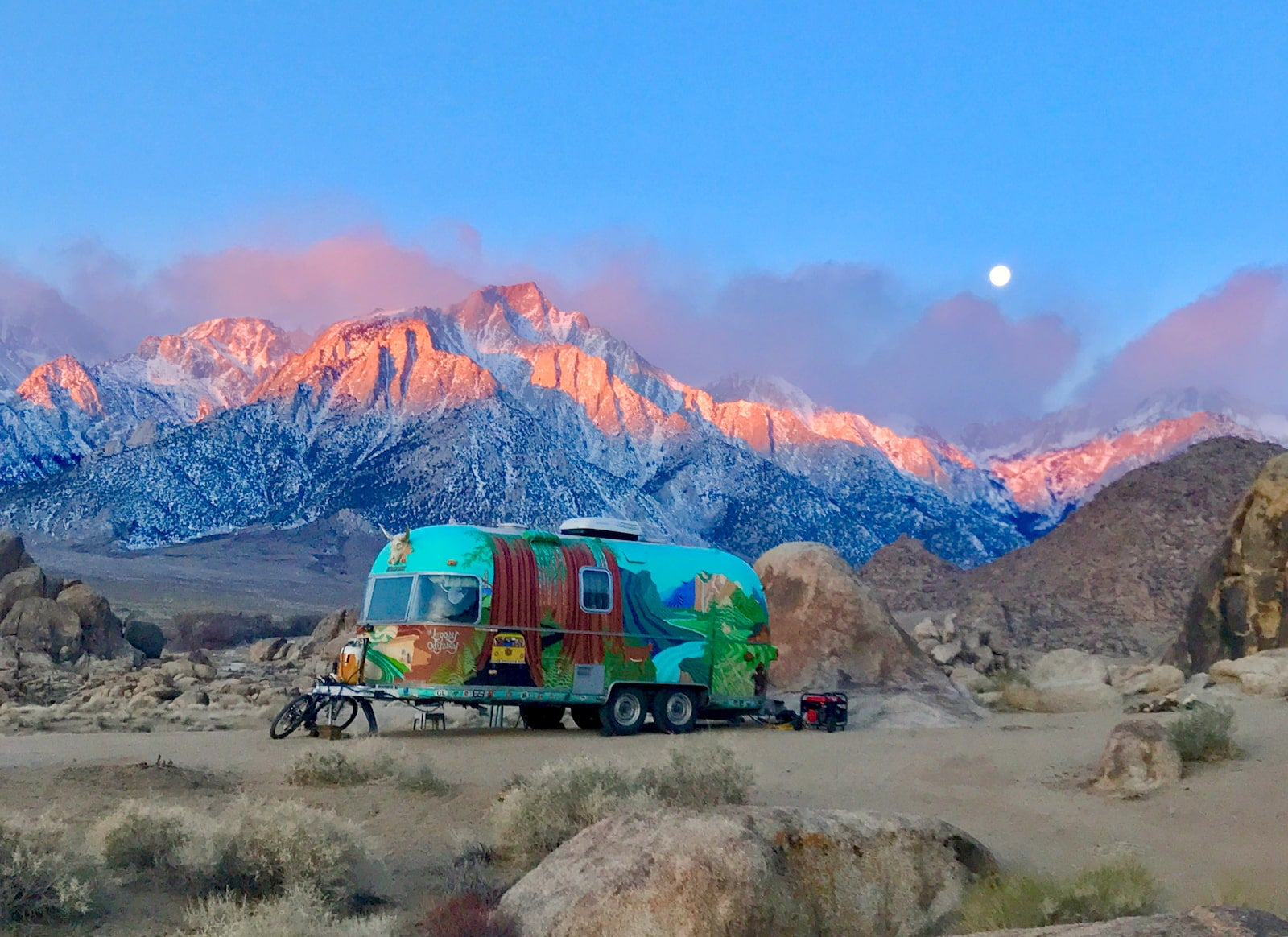 Pink light of dusk hitting snow capped mountains with a painted airstream in the foreground.
