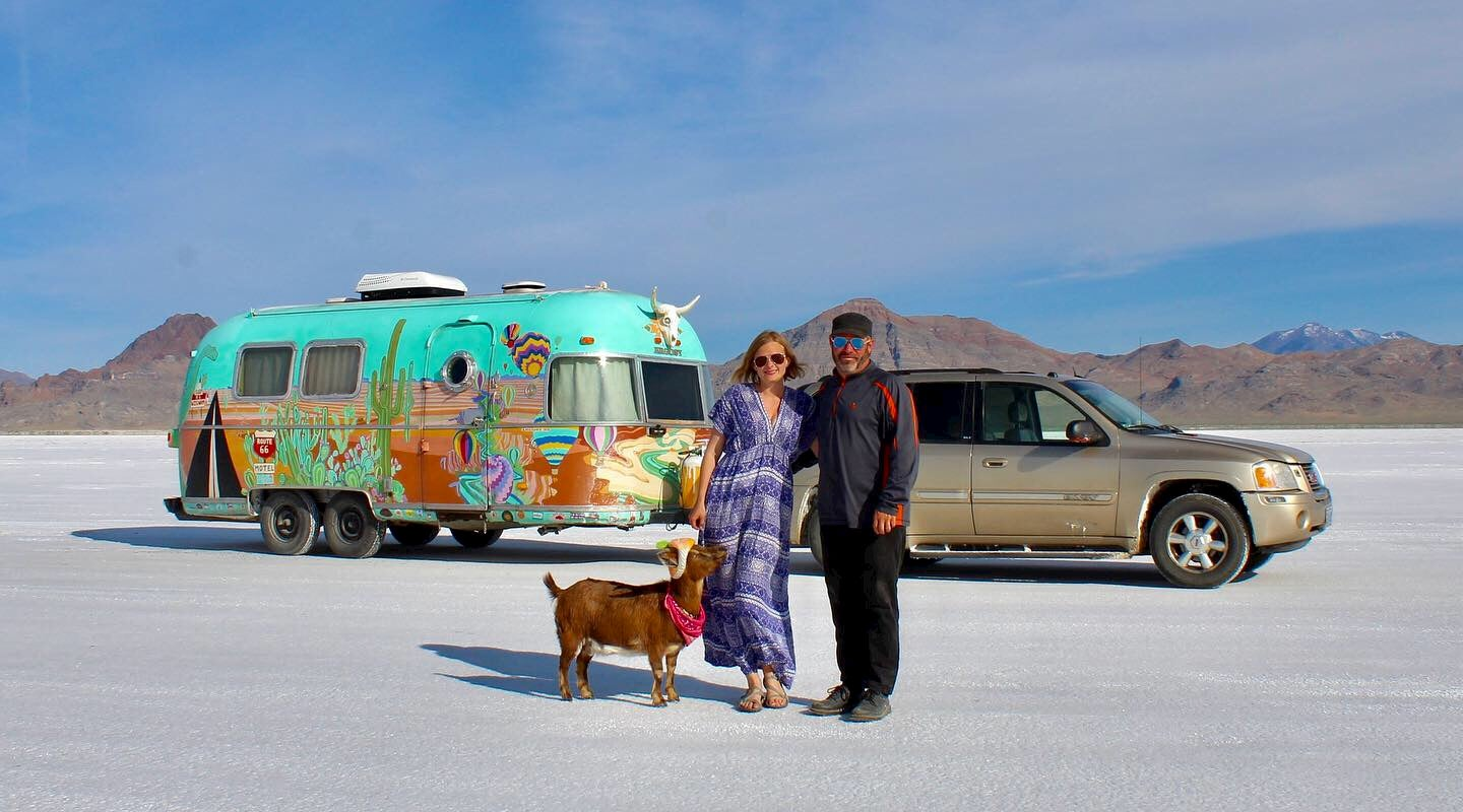 Couple poses in front of airstream with pick up truck and goat on salt flats.
