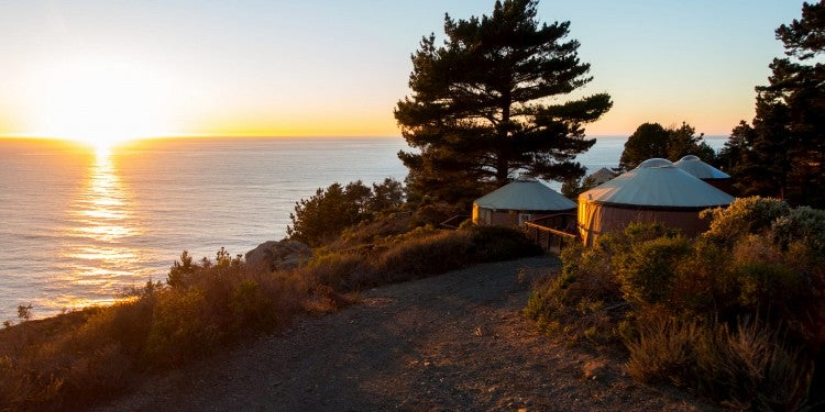 Glamping yurts on the coast of Big Sur at sunset.