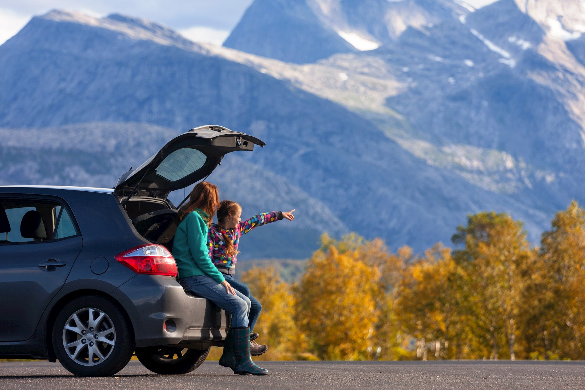 Young girl stand beside her mom in front of a car pointing out into an alpine landscape.