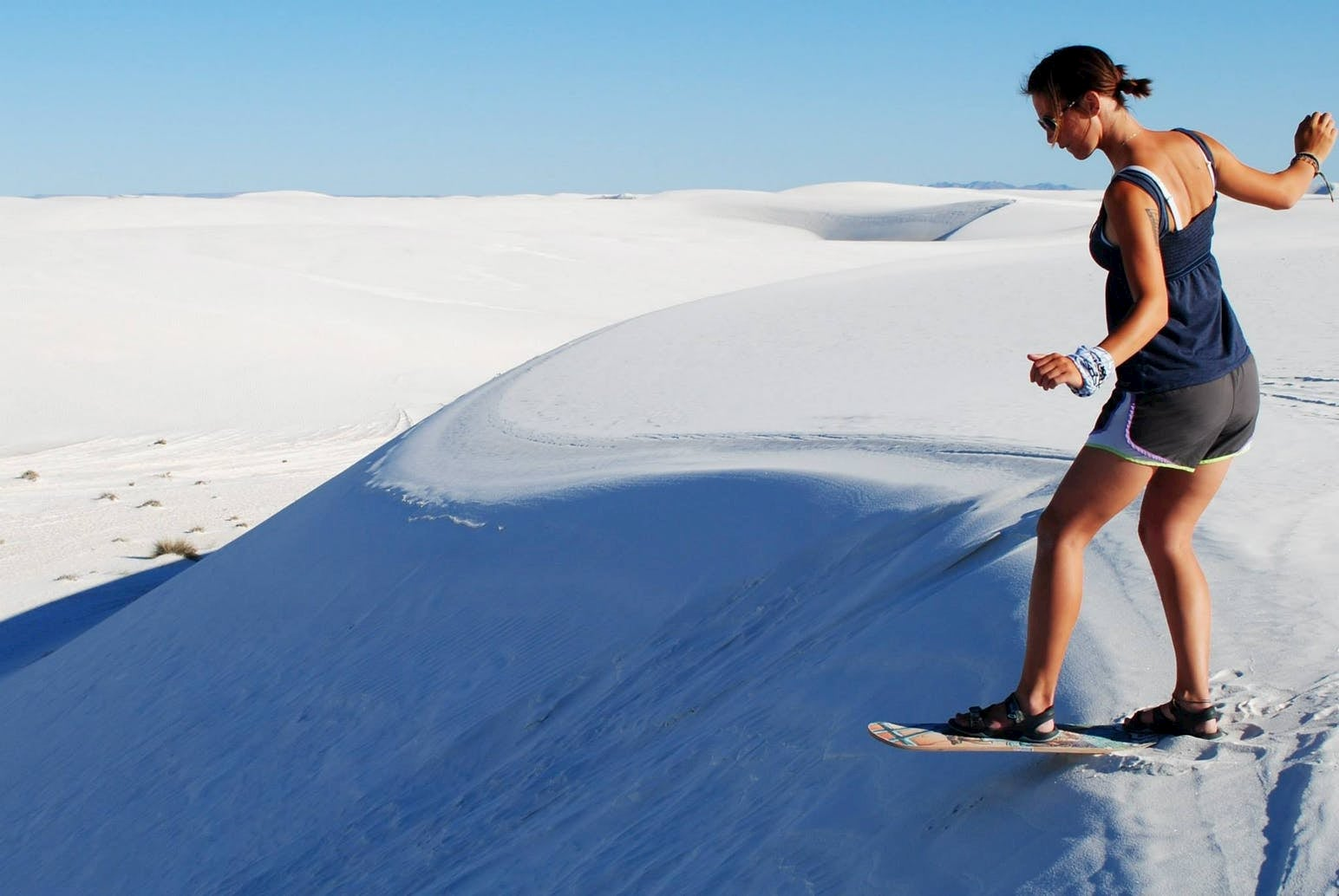 Woman using a sandboard to sled on a sand dune in White Sands National Park.