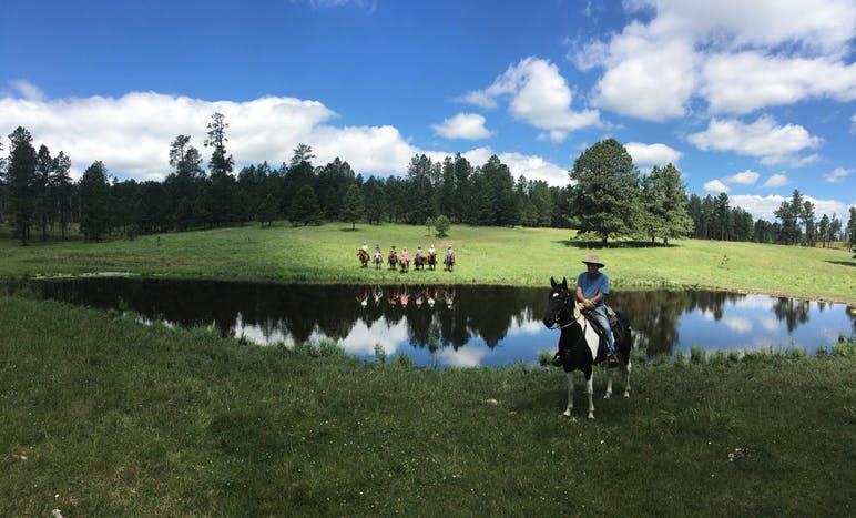 horse riders posing around a pond
