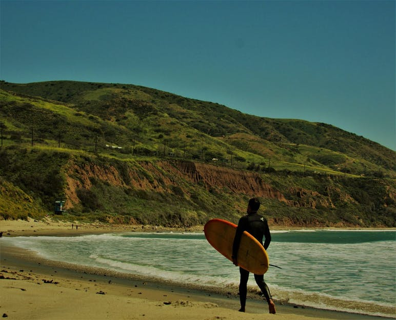 man walking on beach with surfboard