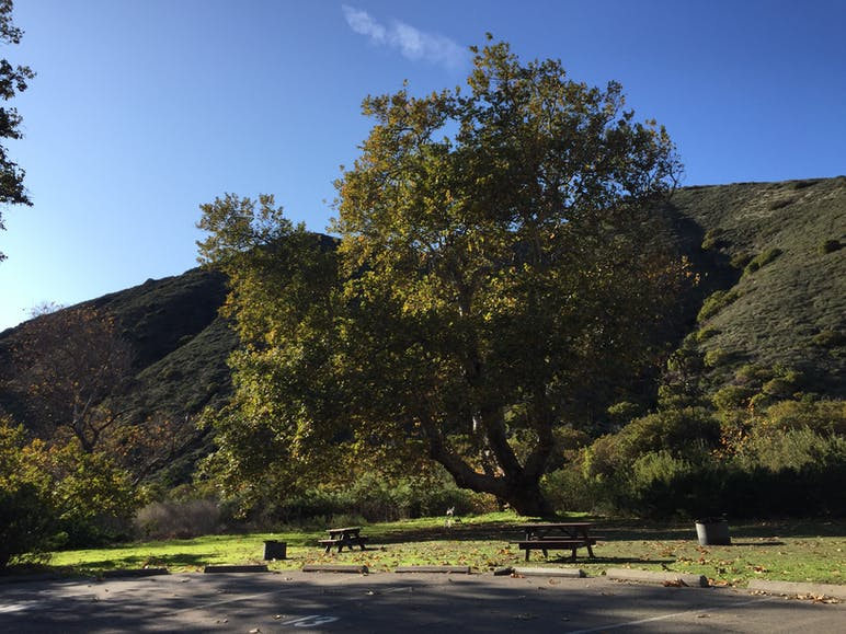 parking lot, picnic benches and hills in the background