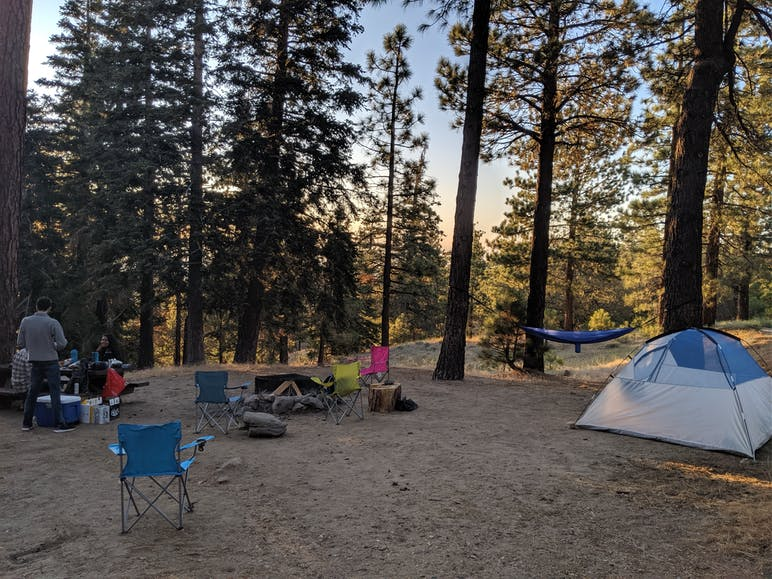 tent, hammock, chairs, and firepit at campsite