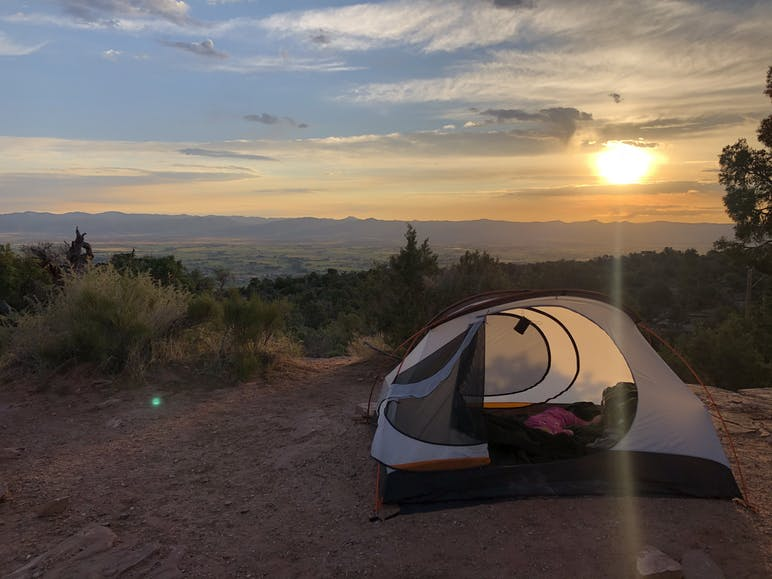 tent with landscape behind it at sunset