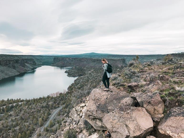 woman overlooking vista and water below