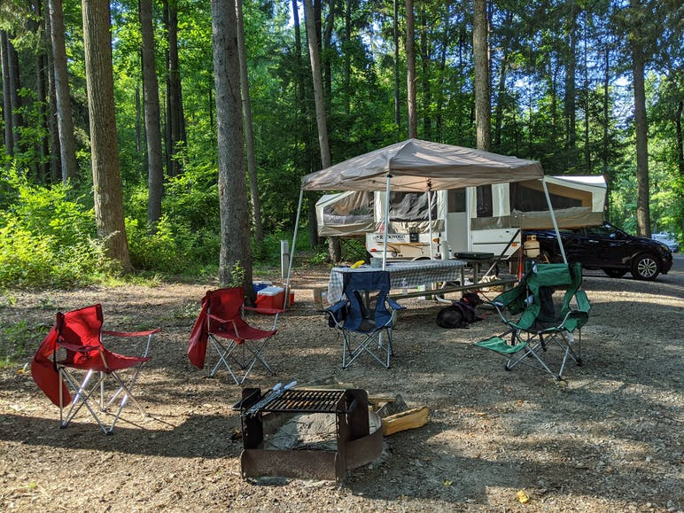 pull-behind camper set up at campsite with chairs around the firepit