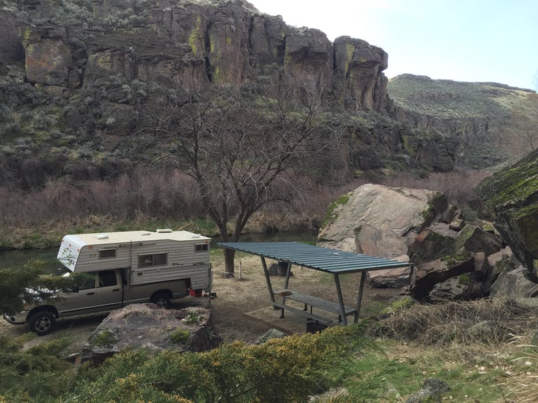 truck parked at campsite with canyon behind