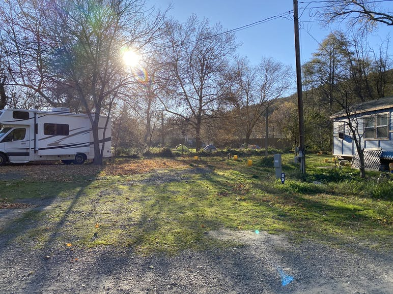 sun shining through trees overlooking two rvs camped