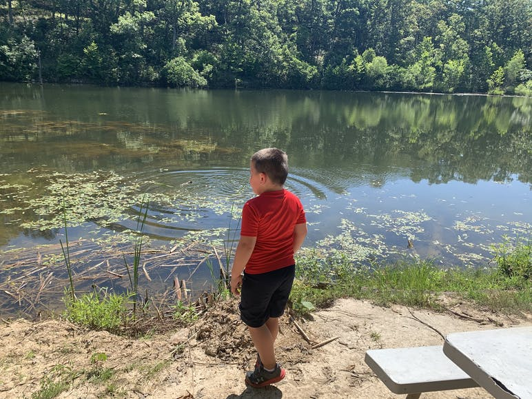 child standing infront of lake