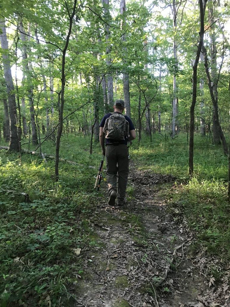hiker walking on trail through woods