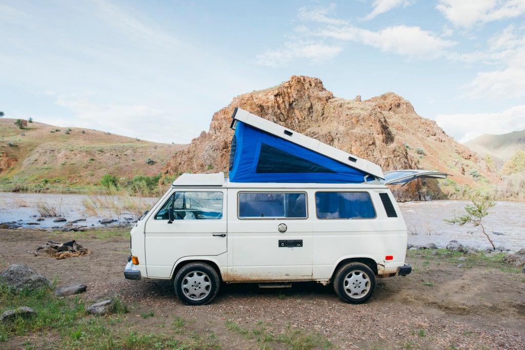 White VW Westfalia van rental in desert landscape.