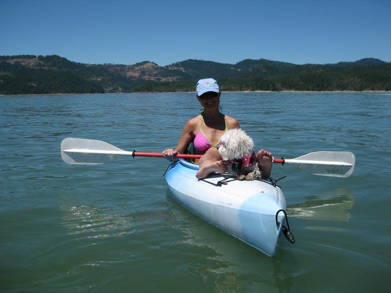 woman in kayak on lake with dog
