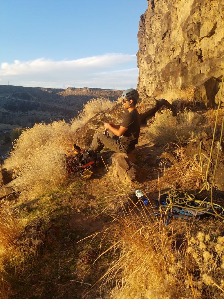 man sitting down getting ready to rock climb