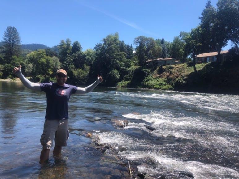 man standing in river enjoying himself