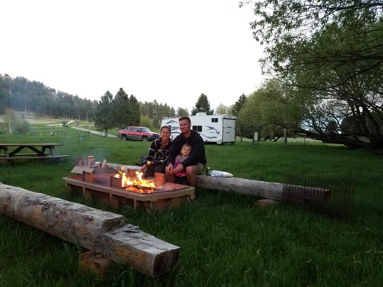 camp guests sitting around a campfire