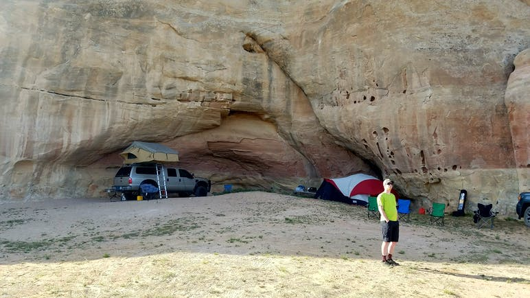 cars parked under large rock face