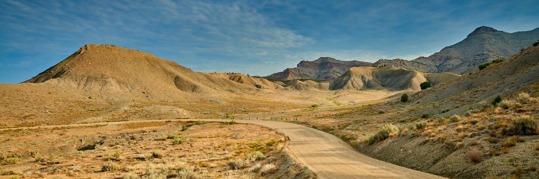 dirt road winding into vast desert valley