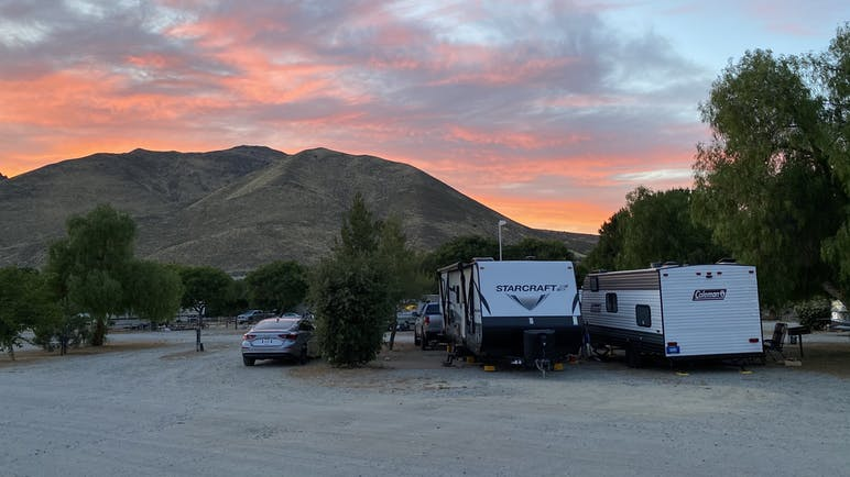 RVs parked at campground at sunset