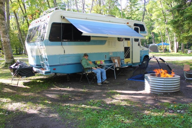 man sitting down outside of camper